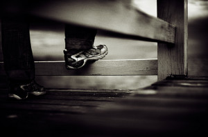Man standing with foot on wooden fence
