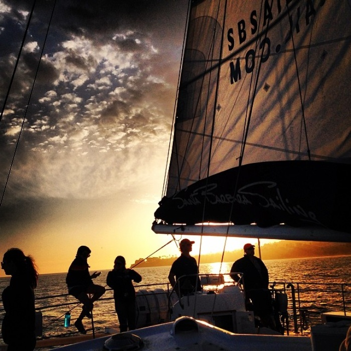 People sailing on a boat into the sun