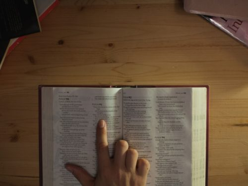 Person pointing to text in an open bible