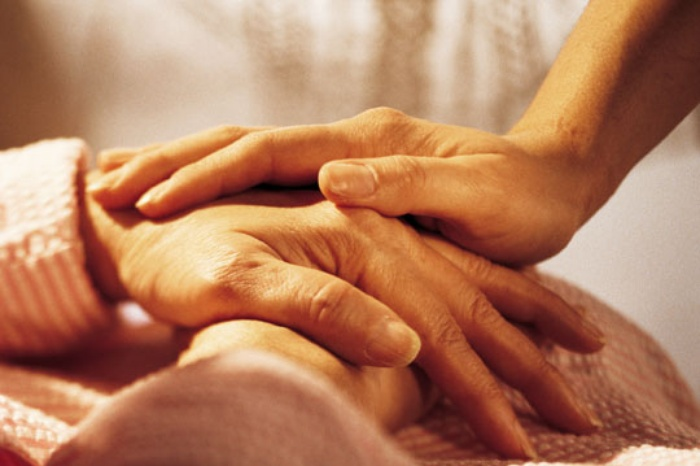 Young woman's hand on top of an elder woman's hands