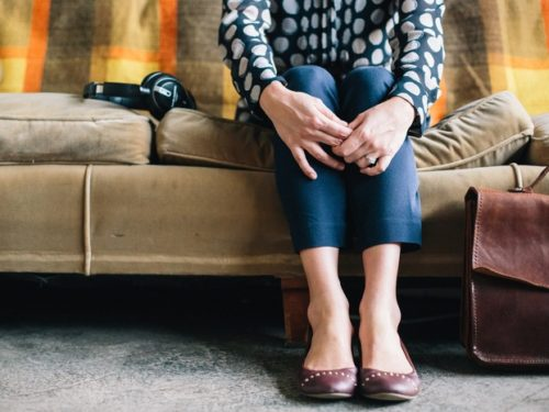 Women sitting on a couch with arms around her knees