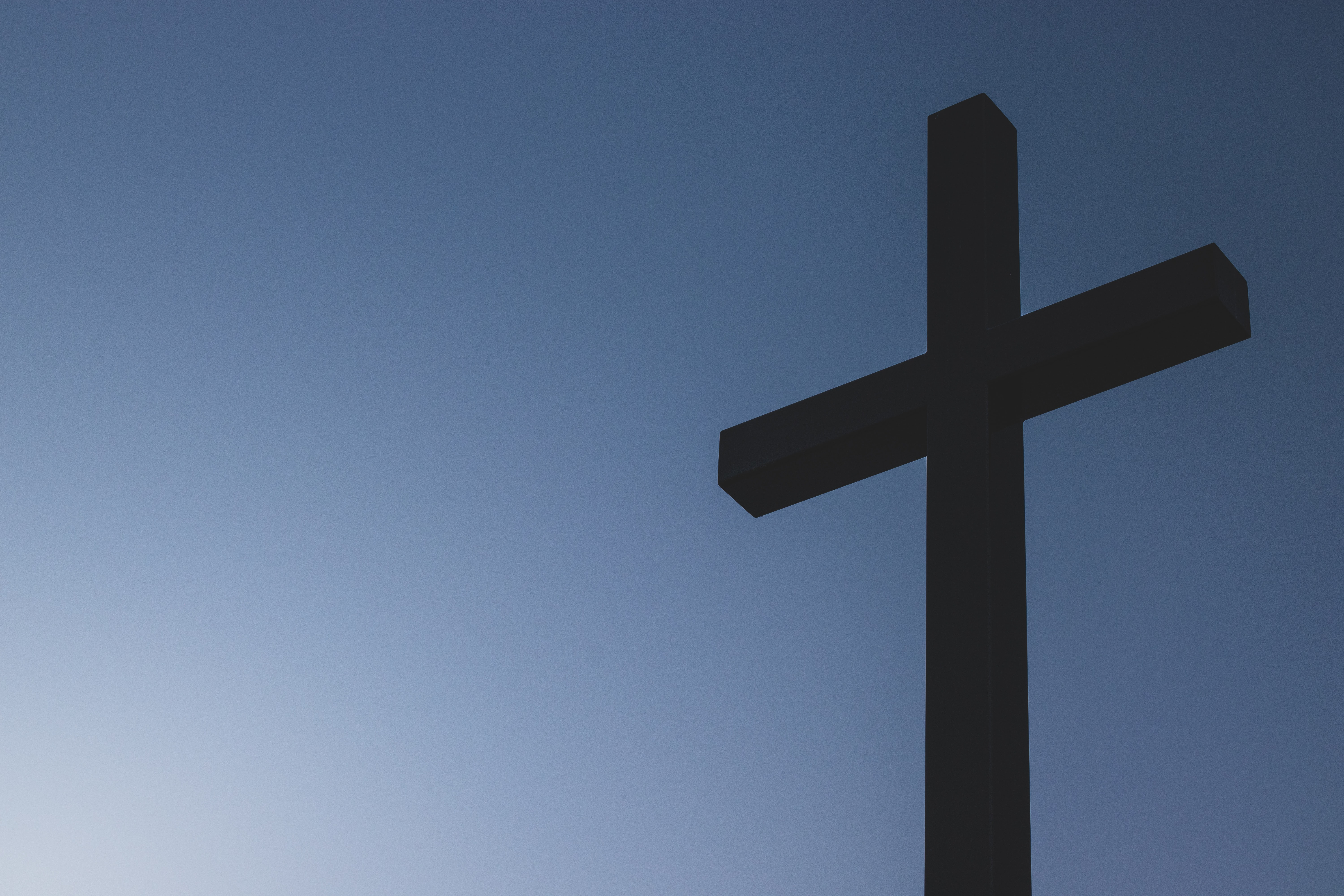 Wooden cross in front of blue sky