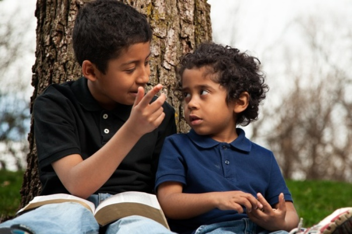 Two young boys sitting in front of a tree reading a book