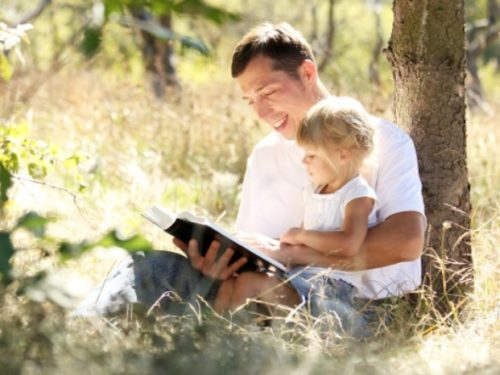 Dad reading to young child outdoors