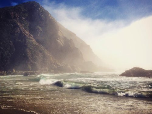 Waves crashing on the sand with mountains in the back