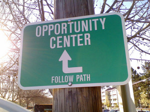 Traffic sign stating opportunity center, follow path