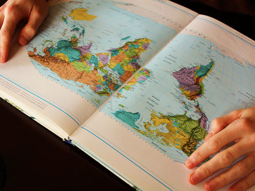 Person looking at open map of the world