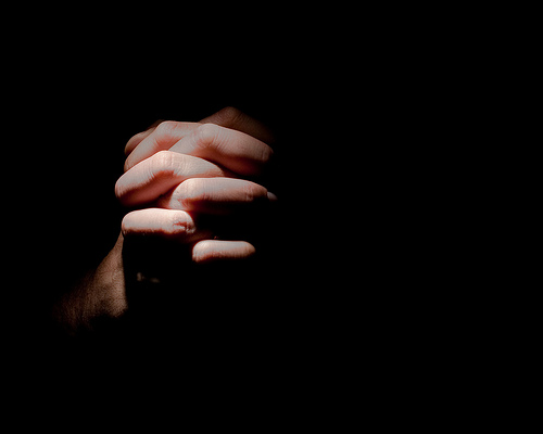 Hands praying in the dark