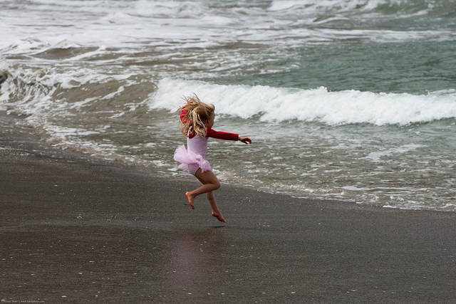 Young girl running into the ocean waves