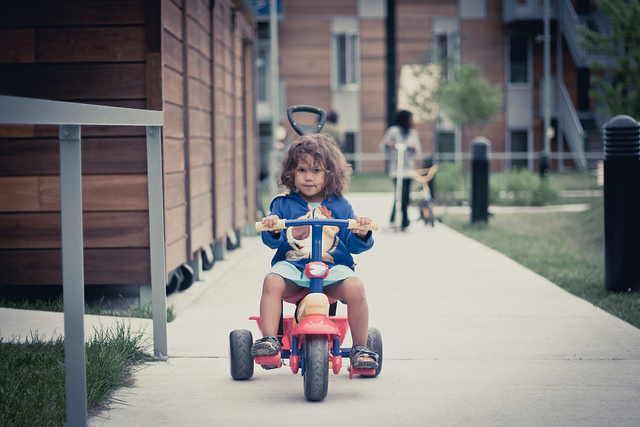 Young child riding a tricycle on a sidewalk