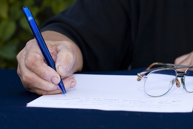 Person writing something on paper with a blue pen