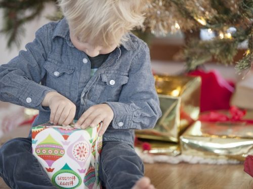 Young child opening a gift on Christmas